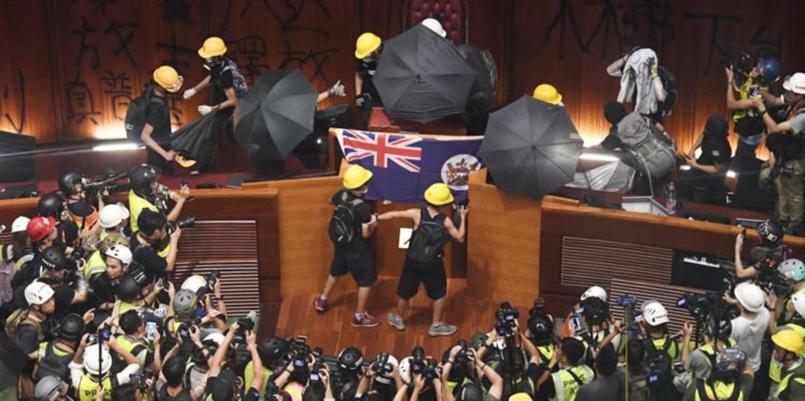 Protesters trashing the Hong Kong legislature, and mounting British flag
